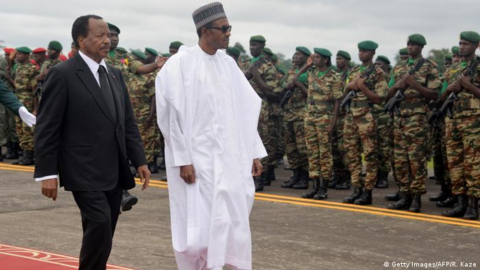 Nigerian President Muhammadu and Cameroonian President Paul Biya march past soldiers parade.
