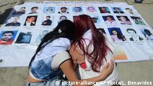 27.07.2015+++ Women look at a poster with images of missing people, during a ceremony to remember the disappeared and kick off a search effort in La Escombrera, on the outskirts of Medellin, Colombia, Monday, July 27, 2015. La Escombrera is a debris landfill where the remains of as many as 300 people are believed to have been dumped during one of the darkest chapters of Colombia¿s long-running civil conflict. Human rights activists say the landfill could prove to be the largest mass grave ever found in Colombia and the dig represents a glimmer of hope that justice will be realized. (AP Photo/Luis Benavides)