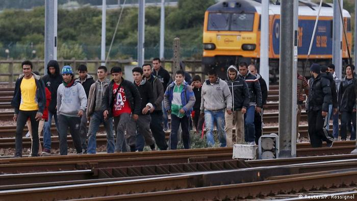 Migrants cross rail tracks to enter the Channel Tunnel