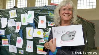 Astrid Raith zeigt ein selbstgemaltes Bild einer Maus. (Foto: DW/J. Semenova)