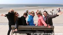 Junge Frauen aus dem Emsland und Ostfriesland genießen am 23.04.2013 bei Temperaturen um die elf Grad Celsius das Frühlingswetter auf der Strandpromenade der ostfriesischen Insel Borkum (Niedersachsen). Foto: Ingo Wagner/dpa +++(c) dpa - Bildfunk+++