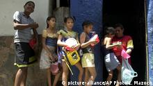 Children wait in line with their food containers during lunchtime at a soup kitchen sponsored by the government of President Hugo Chavez in the impoverished Caracas neighborhood La Vega in Venezuela, Monday, Aug. 2, 2004. After five years in office, President Hugo Chavez remains a hero for millions of Venezuelans who see him as their only hope for a better future, and that gives him a good chance of beating a recall referendum to be held on Aug. 15. (AP Photo/Leslie Mazoch)