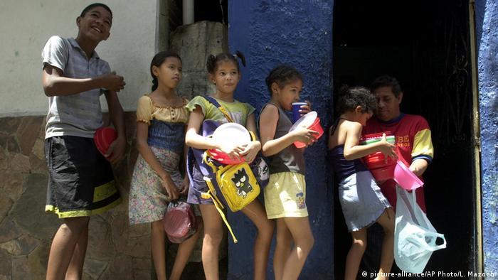 Niños de un barrio marginado en Caracas hacen fila para recibir alimentos.