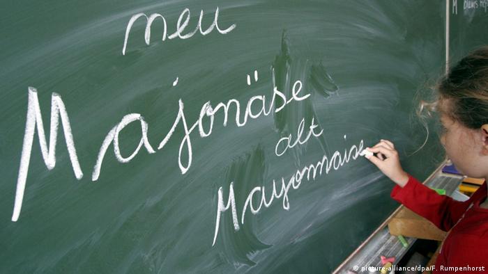 Eine Schülerin schreibt die alte und neue Schreibweise von Majonäse an eine Schultafel: neu: Majonäse, alt: Mayonnaise