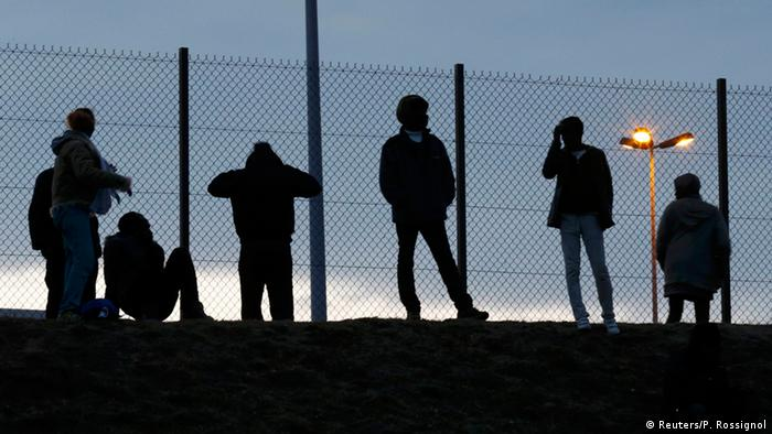 Migrants are seen in silhoutte as they stand on a rise near a fence as they gather near the Channel Tunnel access in Frethun, near Calais, France, July 30, 2015 (Photo: REUTERS/Pascal Rossignol)