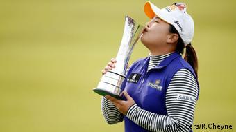 Female golfer kissing trophy