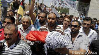 Mourners with the body of a Palestinian baby killed after his family's house was set fire by Israeli settlers