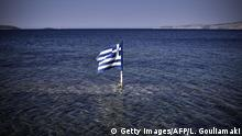 Bildunterschrift:This photo taken on July 29, 2015 shows a Greek flag floating in the sea at the Kalamitsa beach on Skyros island. Greece expects debt reduction from its international creditors after a first assessment of reforms under its new bailout obligations concludes in November, Prime Minister Alexis Tsipras said on July 29. AFP PHOTO/ LOUISA GOULIAMAKI (Photo credit should read LOUISA GOULIAMAKI/AFP/Getty Images)