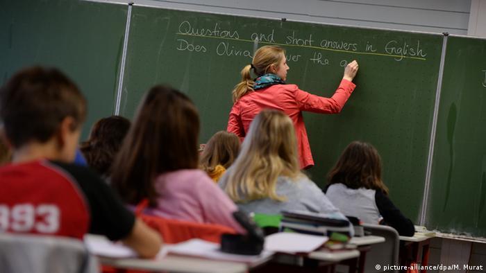 Quatro alunos sentados uns atrás dos outros em sala de aula na Alemanha. Ao fundo, professora escreve questão em inglês numa lousa verde