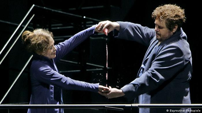 Evelyn Herlitzius and Stephen Gould, arms outstretched, holding hands (Bayreuther Festspiele)