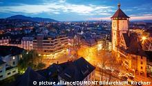 rechts ein altes Rathaus mit Turm, daneben erstreckt sich eine Stadt. Es dämmert und die Straßen sind vom gelben Licht der Laternen erleuchtet.