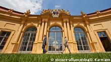 ein Teil der Fassade eines gelbes Barockgebäudes, davor zwei Männer, die nach links gehen (Erlangen Orangerie)