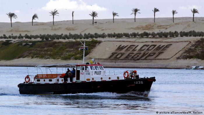 A boat traveling through the Suez Canal in front of a sign reading: Welcome to Egypt