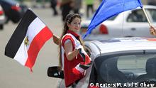 A girl carries a national flag while riding in a car as people gather in Tahrir square to celebrate an extension of the Suez Canal, in Cairo, Egypt, August 6, 2015. Egypt will open an expansion to the Suez Canal to great fanfare on Thursday, the centrepiece of President Abdel Fattah al-Sisi's plans to revitalise the country's economy after years of damaging political turmoil. REUTERS/Mohamed Abd El Ghany