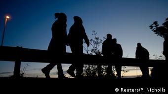 Migrants are seen in silhouette as they walk along the motorway near the Channel Tunnel entrance near Calais