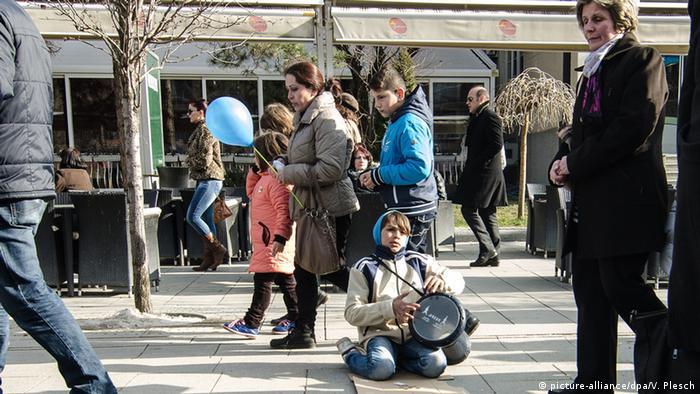 Ein junge mit einer Trommel sitzt auf dem Boden, vor und hinten laufen Passanten an ihm vorbei