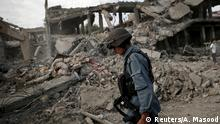 7.8.2015 Afghan policeman walks at the site a truck bomb blast in Kabul, August 7, 2015. A truck bomb exploded near an army compound in Kabul on Friday, killing at least 15 people and wounding another 248, police and government officials said, in the first major attack in the Afghan capital since the Taliban announced a new leader. REUTERS/Ahmad Masood