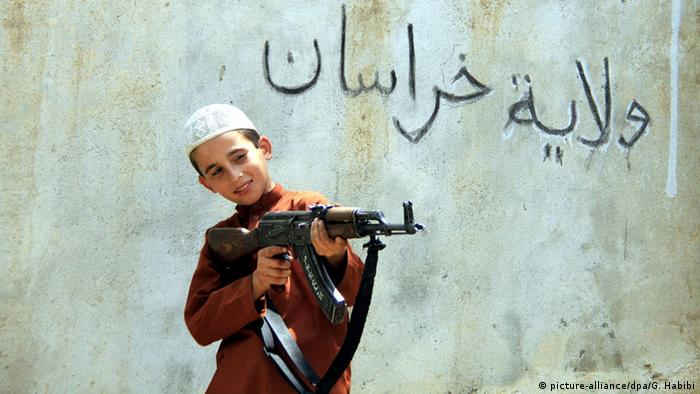 A picture made available on 01 August 2015 shows an unidentified child from a militant of Islamic State (IS) playing with an AK-47 rifle as the text on the wall reads in Arabic 'Islamic State - Khurasan Chapter' at an undisclosed location in Kunar province, Afghanistan, 30 July 2015.