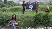 epaselect epa04868675 A picture made available on 01 August 2015 shows an unidentified child from a militant of Islamic State (IS) playing with an AK-47 rifle as the text on the wall reads in Arabic 'Islamic State - Khurasan Chapter' at an undisclosed location in Kunar province, Afghanistan, 30 July 2015. More than 1000 Afghan families have been displaced by clashes in the Achin and Spinghar districts in eastern Afghanistan between armed opposition groups, some allegedly claiming allegiance to the group calling themselves the Islamic State (IS) after defecting from the Taliban. EPA/GHULAMULLAH HABIBI