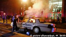 epa04877911 (FILE) A file photo dated 25 November 2014 of a police officer extinguishing a fire after protesters tried to burn a Ferguson Police car in front of City Hall the night after protesters burned buildings in protest of the Grand Jury decision not to indict police officer Darren Wilson in shooting death of Michael Brown in Ferguson, Missouri, USA. One year ago, on 09 August 2014, a white policeman in Ferguson, Missouri, shot unarmed black teenager Michael Brown. His death and subsequent killings by police around the country of other unarmed blacks triggered riots, protests and outrage over police brutality. EPA/LARRY W. SMITH *** Local Caption *** 51678271