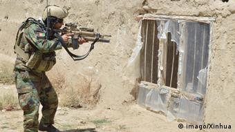 Afghan soldier pointing gun at window in a wall.