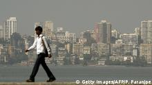 Bildunterschrift:The Mumbai city skyline is seen as a pedestrian walks past the seaside promenade in Mumbai on January 12, 2012. The construction of enormous skyscrapers has an 'unhealthy' link with looming financial crises and investors should therefore keep a close eye on China and India, Barclays Capital said on January 11. China is currently the biggest builder of skyscrapers, while booming India is constructing the second largest tower in the world, the investment bank said in its latest annual 'Skyscraper Index' survey. AFP PHOTO/Punit PARANJPE (Photo credit should read PUNIT PARANJPE/AFP/Getty Images)