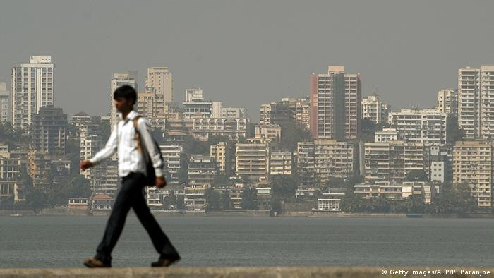 The Mumbai city skyline towers above a pedestrian walking past the seaside promenade.