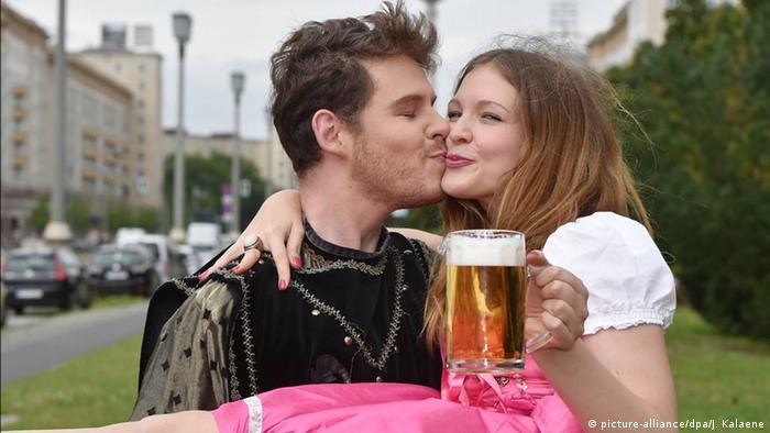 Молодой человек держит на руках девушку с кружкой пива