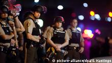 10.08.2015 *** epa04878919 Officers from the St. Louis County Police, wearing riot gear, guard the perimeter of the scene of an officer-involved shooting on West Florissant Avenue in Ferguson, Missouri, USA, 10 August 2015. A march in Ferguson was disrupted by gunfire on the anniversary of the shooting death of unarmed African-American teenager Michael Brown by white police officer Darren Wilson. Half a dozen shots were heard on footage broadcast by the BBC, prompting hundreds of people to flee the previously peaceful protests. One person was injured, the report said. The memorial event began earlier with four-and-half-minutes of silence, to mark the four-and-a-half hours that his body was left in the street while police gathered crime scene evidence. The death of Brown on 09 August 2014 sparked a series of protests that helped create a renewed interest in civil rights in the United States. EPA/SID HASTINGS