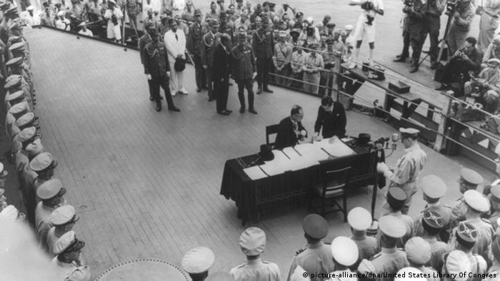 Foto histórica com duas pessoas de roupas pretas junto a uma mesa e vários militares em volta