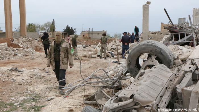 Rebel fighters walk through the rubble following an alleged bombing by Islamic State (IS) group in Marea, northern Aleppo on April 8, 2015 (Photo: ZEIN AL-RIFAI/AFP/Getty Images)