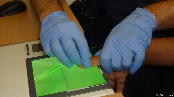 Police officer takes finger prints from an asylum seeker in Rosenheim, southern Germany