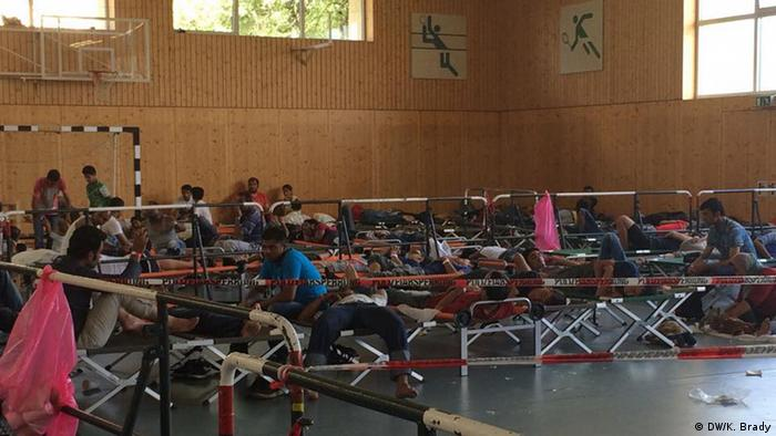 Newly-arrived asylum seekers rest in a shelter set up in a sports hall in Rosenheim, Bavaria