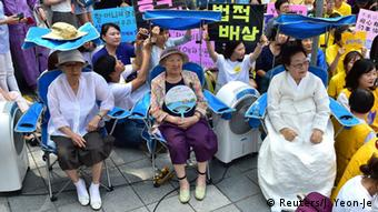(L-R on blue chairs) South Korean former 'comfort women' Kim Bok-Dong, Gil Won-Ok and Lee Yong-Soo, who were forced to serve as sex slaves for Japanese troops during World War II, attend a protest with other supporters to demand Tokyo's apology for forcing women into military brothels during World War II outside the Japanese embassy in Seoul on August 12, 2015 (Photo: JUNG YEON-JE/AFP/Getty Images)