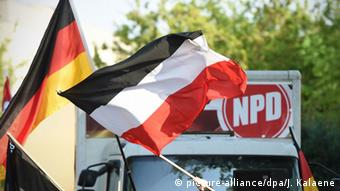 German flags in front of an NPD sign. (Photo: Jens Kalaene/dpa)