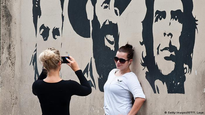 Tourists pose for pictures in front of graffitis of images of revolutionary leaders in Havana.