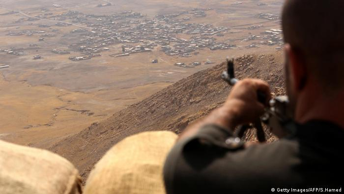 An Iraqi Kurdish Peshmerga fighter monitors his surroundings from the top of Mount Zardak, about 25 kilometres east of Mosul