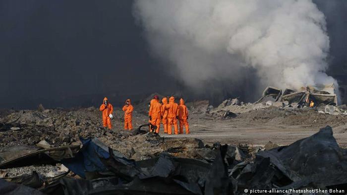 China Arbeiter in Schutzanzügen auf dem verwüsteten Hafengelände von Tianjin