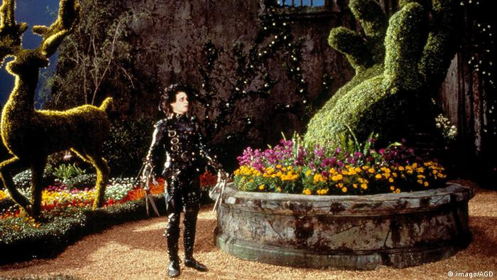 Johnny Depp as Edward Scissorhands in Tim Burton's movie of the same name shows him with scissors for hands in front of a hedge trimmed to look like a deer (imago/AGD)