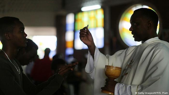 A Catholic priest in Burundi performs communion in church (Getty Images/AFP/S. Platt)