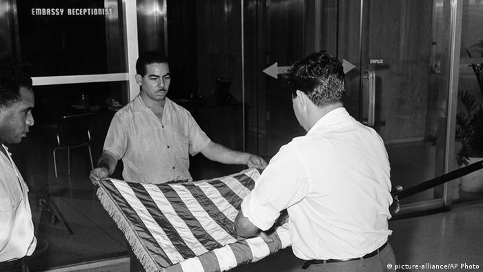 Zwei Mitarbeiter der US-Botschaft in Havanna rollen die US-Flagge zusammen (Foto: picture-alliance/AP Photo)