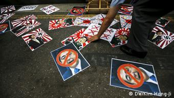 A man scatters posters depicting Japanese Prime Minister Shinzo Abe during an anti-Japan rally on the occasion of the 70th anniversary of liberation from Japan's 1910-45 colonial rule, on Liberation Day in Seoul, South Korea, August 15, 2015 (Photo: REUTERS/Kim Hong-Ji)