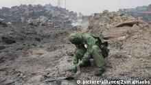 TIANJIN, Aug. 15, 2015 A soldier of National Nuclear Biochemical Emergency Rescue Team obtains soil samples in a rescue mission at the core area of explosion site in Tianjin, north China, Aug. 15, 2015. Death toll rose to 85 as of Friday night, including 21 firemen, from the massive warehouse explosions hitting north China's Tianjin City Wednesday night, the rescue headquarters said Saturday. Meanwhile, 721 others were hospitalized, including 25 critically wounded and 33 in serious condition