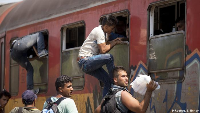 Migrants board a train through the windows at Gevgelija train station in Macedonia, close to the border with Greece, August 15, 2015.