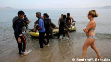 August 15, 2015 A Spanish tourist watches Pakistani migrants arriving at a beach in the Greek island of Kos after paddling an engineless dinghy from the Turkish coast August 15, 2015. United Nations refugee agency (UNHCR) called on Greece to take control of the total chaos on Mediterranean islands, where thousands of migrants have landed. About 124,000 have arrived this year by sea, many via Turkey, according to Vincent Cochetel, UNHCR director for Europe. REUTERS/Yannis Behrakis