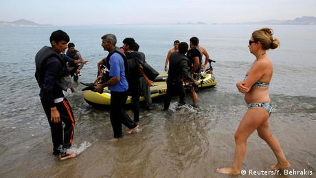 Flüchtlinge kommen an, Touristin läuft vorbei (Foto: REUTERS/Yannis Behrakis)