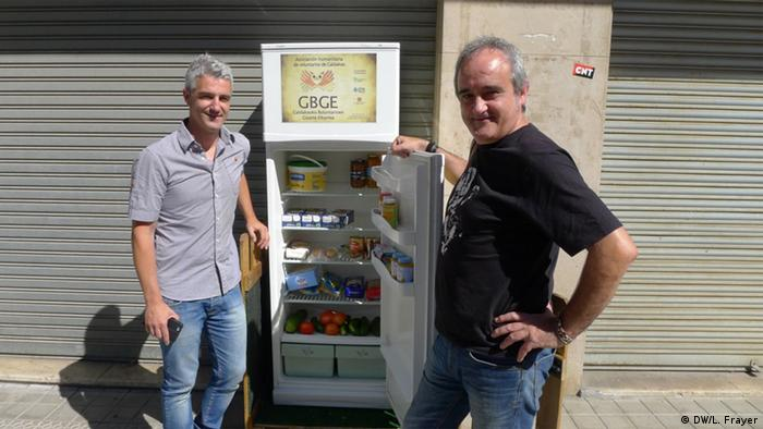 Galdakao's mayor, Ibon Uribe (left), and volunteer Javier Goikoetxea (right), pose in front of the city's Solidarity Fridge, Spain's first communal refrigerator - part of a pioneering project to cut down on food waste and share (Photo: Lauren Frayer)