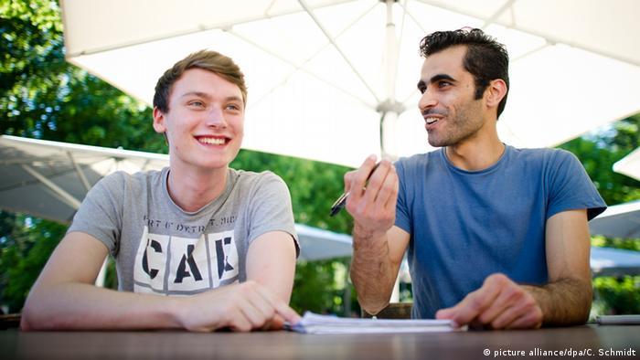 Студент Тим Шварц разговаривает с беженцем из Сирии