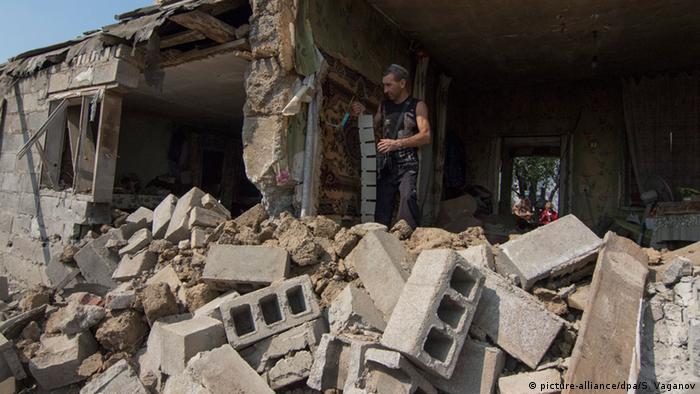 A man stands on debris in a destroyed house after shelling in a territory controlled by the Ukrainian army near the eastern city of Mariupol, Ukraine