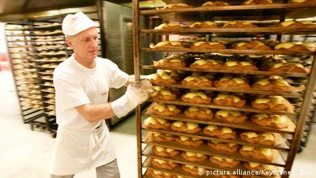 ein Bäcker schiebt einen Wagen voller Bleche mit Puddingteilchen